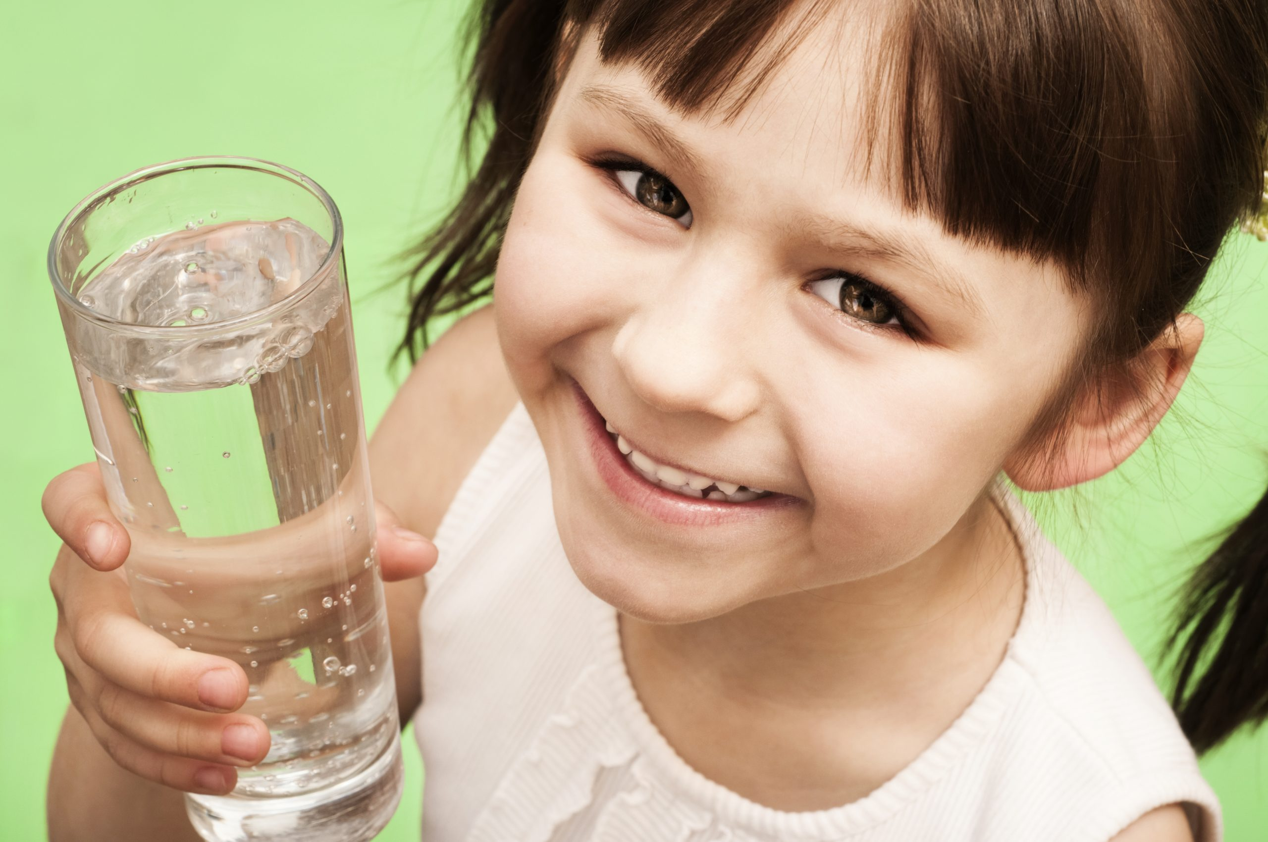Portrait of a little girl with glass of water