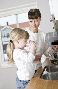 Mutter mit Tochter, die ein Glas Wasser trinkt
